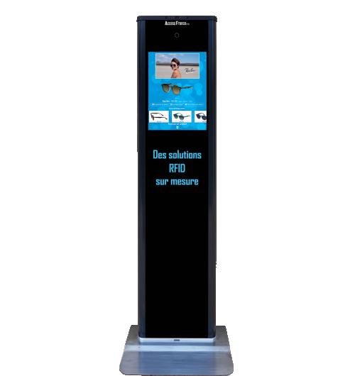 Totem Aide à la vente RFID- Essayage virtuel - Interactif - Affichage dynamique d'informations produit destinés à la clientèle.  Le totem RFID est une borne interactive qui permet d'afficher des informations en lisant les produits à distance grâce à la technologie RFID ou en parcourant les produits disponibles. Attractive et ludique, cette borne permet de faire patienter le client et de le guider dans son choix tout en proposant de l'interactivité sur un support numérique dans votre magasin.  Grâce au totem, le client est autonome et peut :  Lire un produit et consulter ses caractéristiques. Parcourir les produits du catalogue et/ou de votre sélection. Réaliser l'essayage virtuel des produits ou des coloris indisponibles dans le magasin. Se prendre en photo avec les produits. Obtenir des conseils de visagisme (à venir).